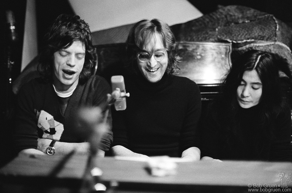 (L-R) Mick Jagger of The Rolling Stones, John Lennon and Yoko Ono singing at a piano at The Record Plant, NYC. 1972. © Bob Gruen / www.bobgruen.com