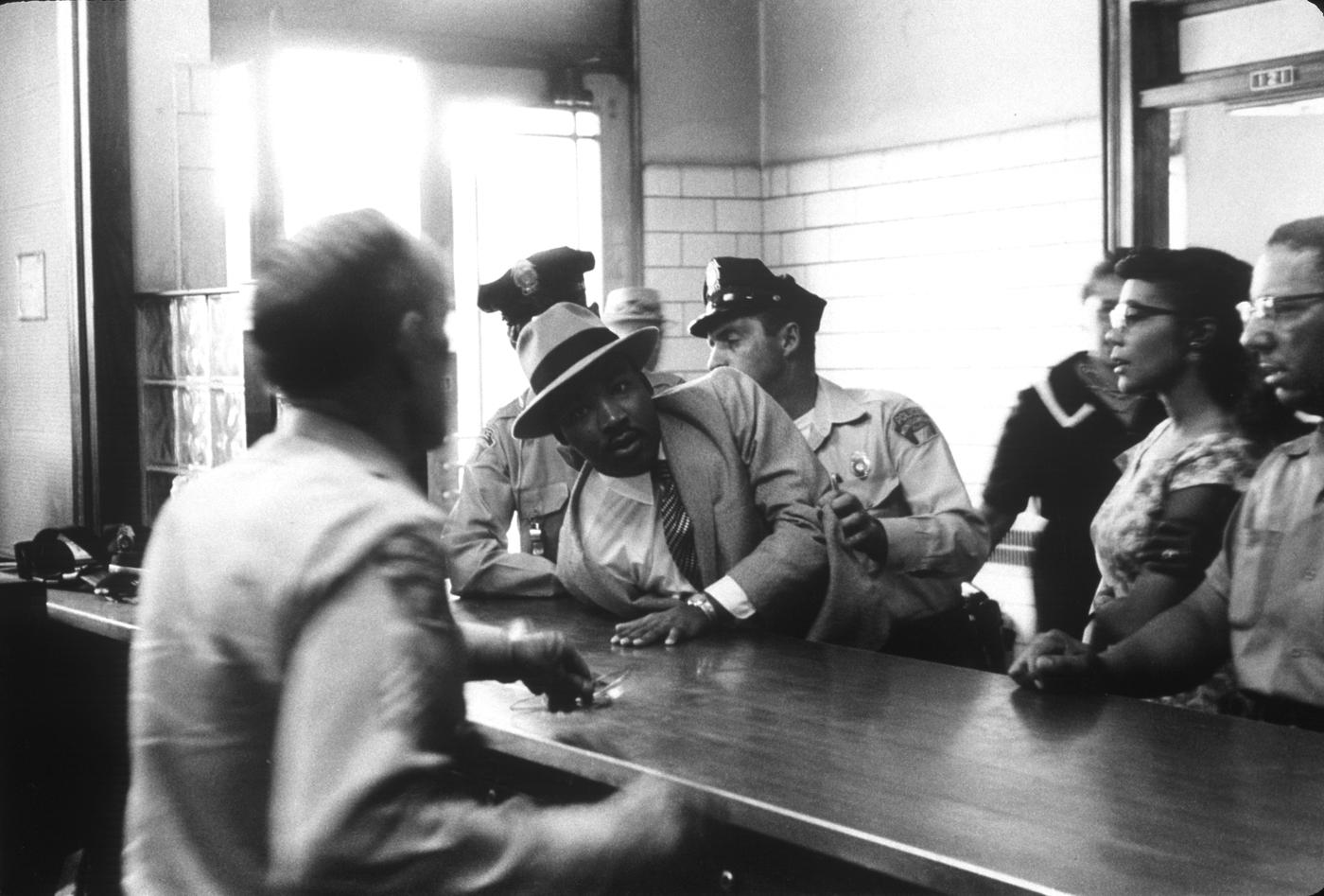 Martin Luther King arrêté devant la tribunal de Montgomery en 1958, sous les yeux de sa femme. Crédit photo : Charles More / black Star