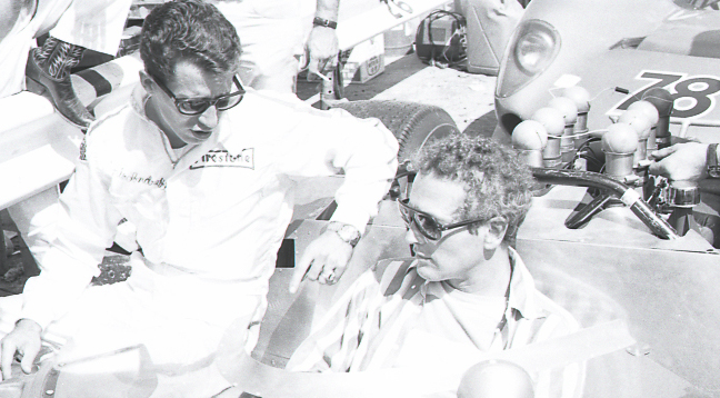 Mario-Andretti-left-and-Paul-Newman-chat-while-seated-on-Paul-Newman's-race-car-at-a-Can-Am-road-racing-event-at-the-famed-Bridgehampton-circuit-on-New-York's-Long-Island-in-September-1967